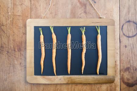 five carrots on blackboard still life