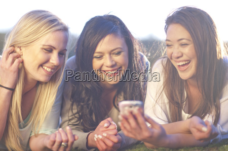 three young women looking at mobile