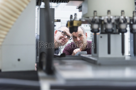 two factory workers checking factory equipment