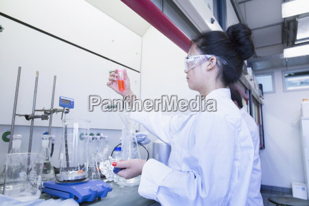 young female scientist holding up orange