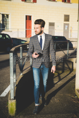 stylish young man with smartphone walking