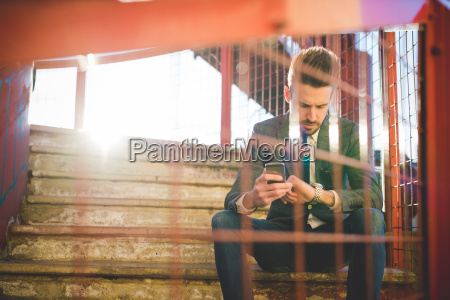 stylish young man with smartphone checking