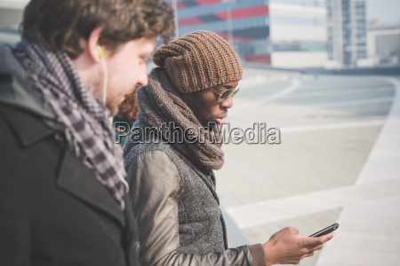 two young men reading smartphone message