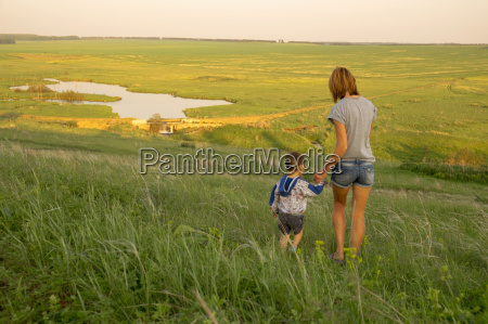 mother and son walking through field