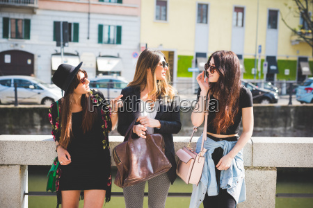 three stylish young female friends chatting