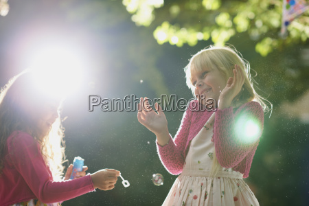 two girls blowing and popping bubbles