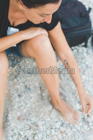 woman playing with pebbles on beach