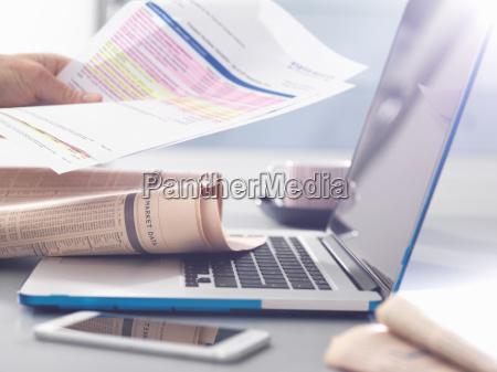 man reviewing financial affairs using newspaper
