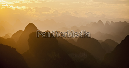 silhouetted sunset over limestone hills guangxi