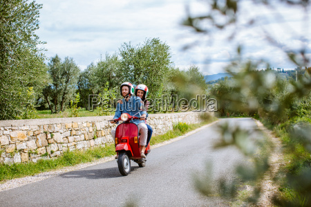 young couple riding moped past olive