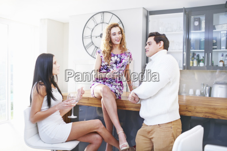 three young adult friends drinking white