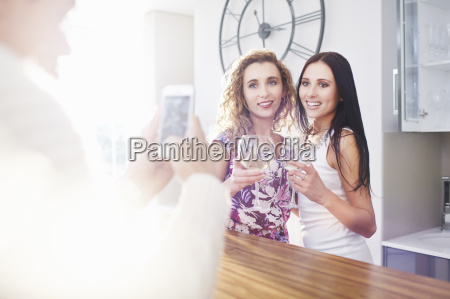 young man photographing female friends on