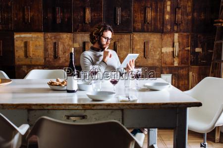 young man reading digital tablet at
