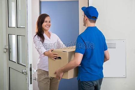 delivery man gibt paket zu frau