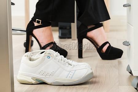 sport shoes besides businesswomans foot