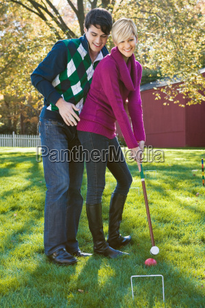 young couple playing croquet