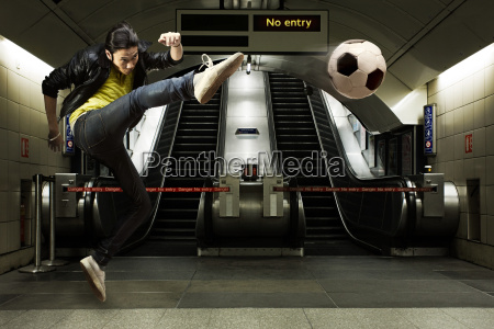 a young man kicking a football