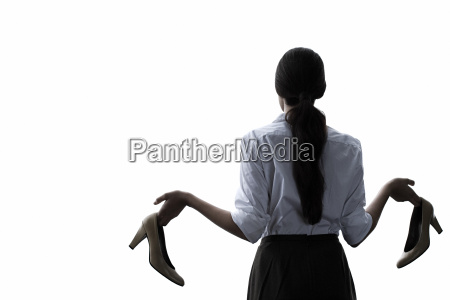 a businesswoman holding high heeled shoes