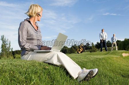 a businesswoman watching colleagues playing golf