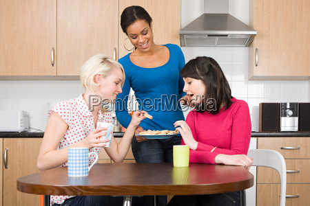 three women having tea and biscuits