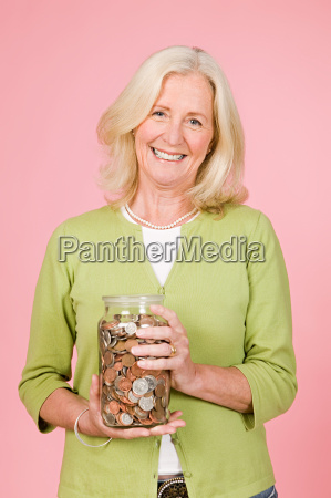 woman holding jar of coins