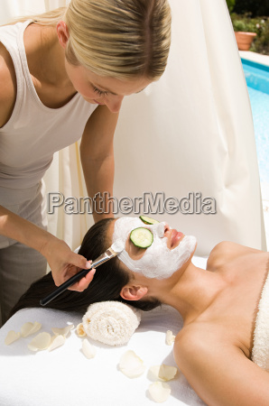 a beautician applying a face mask