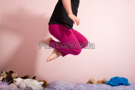 child jumping on a bed