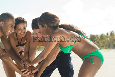 friends on beach with hands together