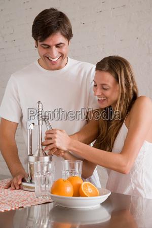 a couple making orange juice