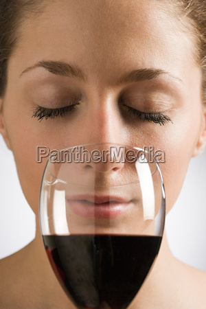 a woman smelling red wine