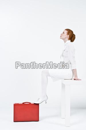 a businesswoman sitting on a desk