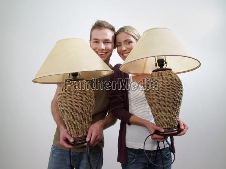 portrait of a couple holding lamps