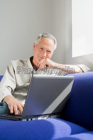 a senior man using a laptop