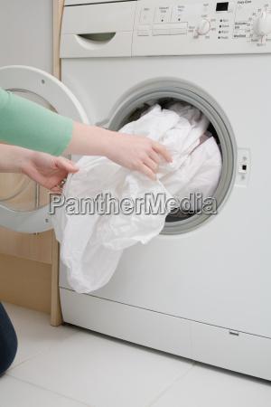 woman taking sheet from washing machine