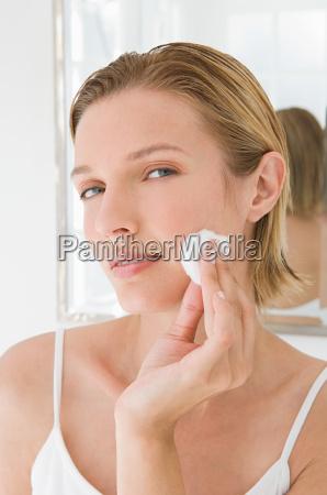 a woman applying make up
