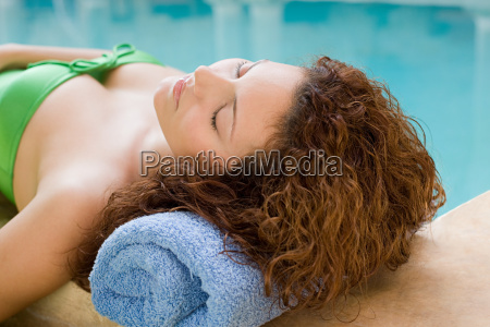 young woman lying by pool