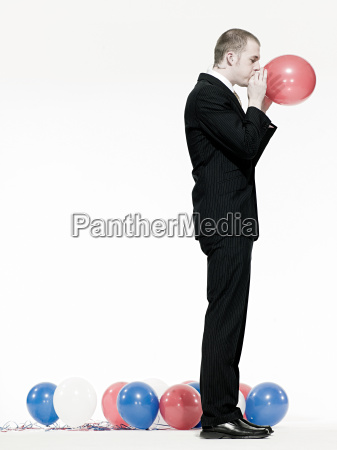 man blowing up balloon