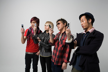 four people using camera telephones