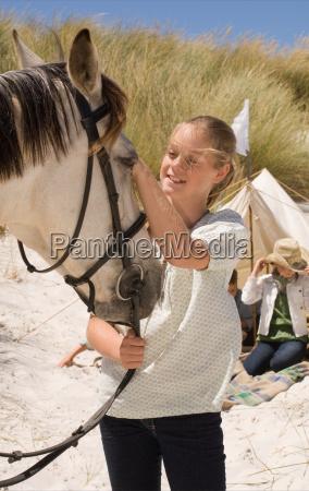 a girl stroking a horse