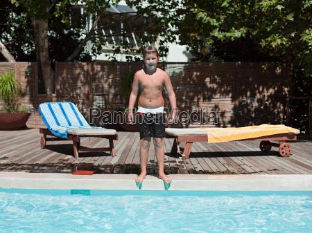 boy on edge of swimming pool