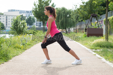 young woman stretching in park