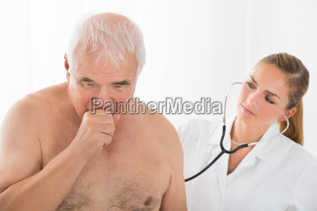 doctor using stethoscope on patients back