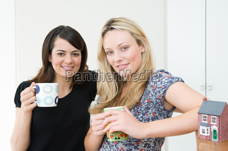 women with coffee cups and model