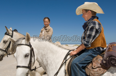 a boy and girl riding horses