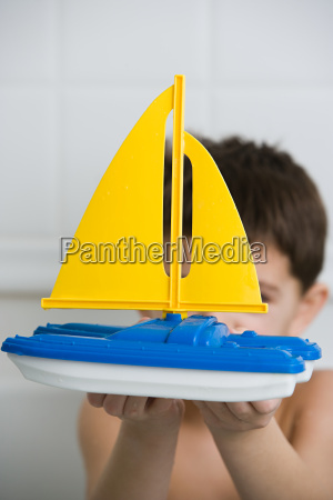 boy holding a toy boat