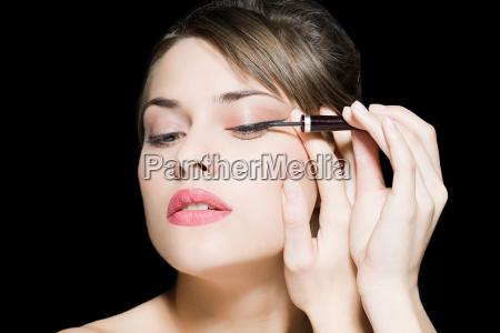 frau die eyeliner aufwendet