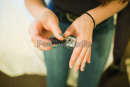 teenage girl painting fingernails with nail