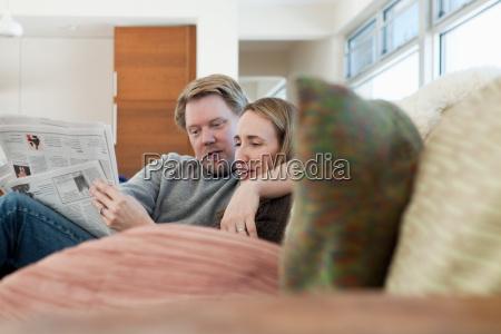couple sitting on sofa reading newspaper