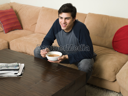 man on sofa with soup