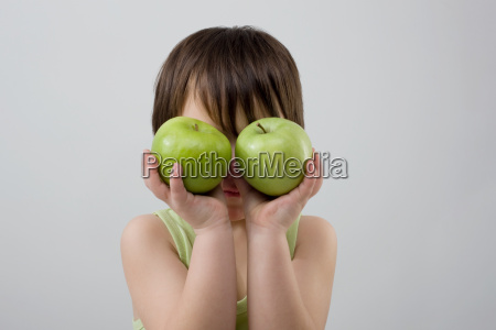 child holding two apples